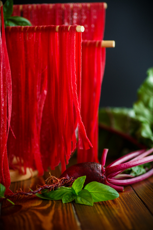cooked instant noodle: Home red noodles from beet juice on a wooden table