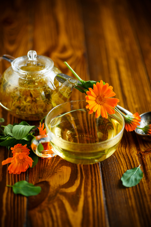 Therapeutic tea from flowers of calendula in a glass teapot Stock Photo