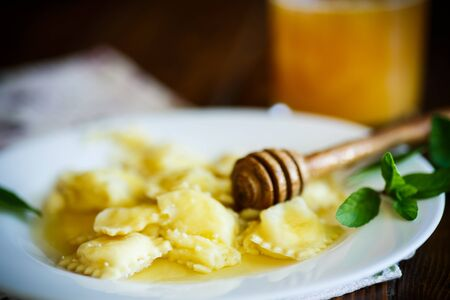desk: Homemade sweet ravioli with cottage cheese and honey Stock Photo