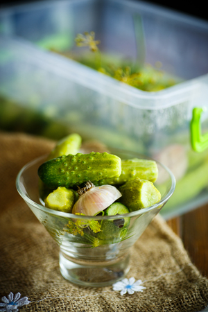 desk: Pickled cucumbers in a glass bowl on a wooden table Stock Photo