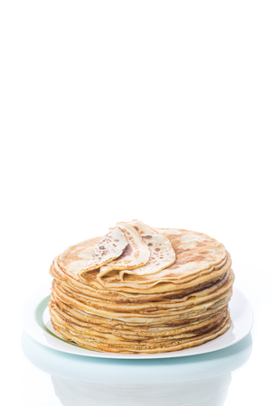thin delicious pancakes in a plate on a white background
