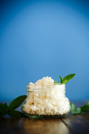 Fresh homemade cottage cheese in a glass jar on a blue background Stock Photo