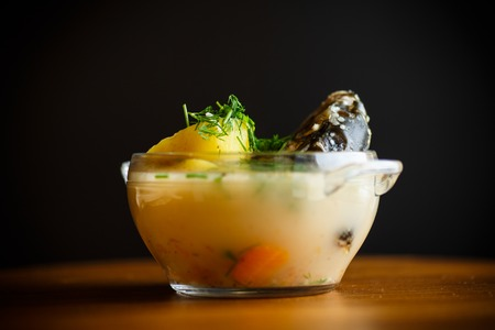 vegetable soup with fish in a glass bowl on a wooden table Standard-Bild