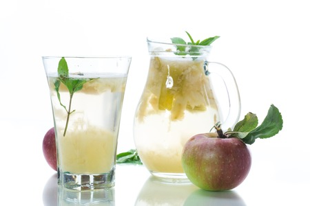 summer sweet cold compote of fresh apples with a sprig of mint in a glass decanter