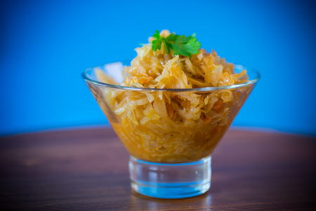 stewed cabbage with carrots in a glass bowl on a blue background Stock Photo