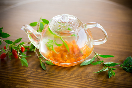 hot tea from ripe red goji berries in a glass teapot on a wooden table