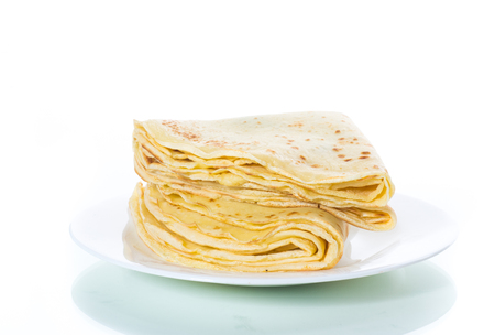 many thin fried pancakes in a plate on a white background