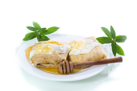 sweet pancakes with cottage cheese, sour cream and honey in a plate