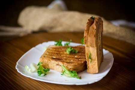 hot double sandwich with lettuce leaves and stuffed in a plate on a wooden table