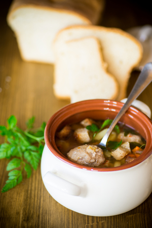vegetable soup with beans and meatballs in a ceramic bowl on a white wooden table Фото со стока