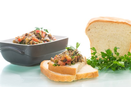 eggplant caviar with tomatoes and a slice of bread isolated on white background