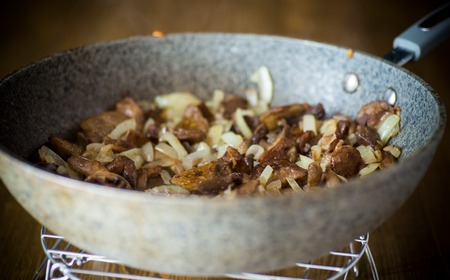 organic forest mushrooms fried with onions in a pan on a wooden table