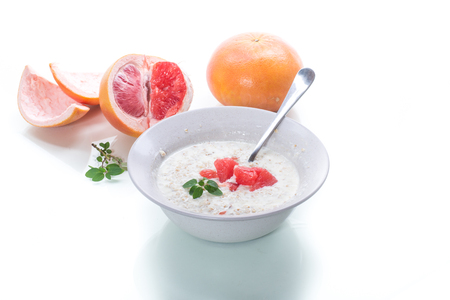 sweet oatmeal with slices of red grapefruit in a ceramic bowl isolated on white background