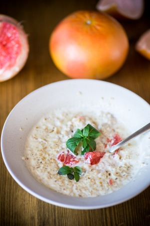 sweet oatmeal with slices of red grapefruit in a ceramic bowl