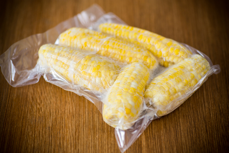 vacuum-packed fresh corn on a wooden table 스톡 콘텐츠