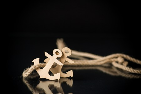wooden decorative anchor on a black background 版權商用圖片