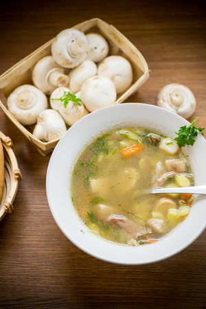 homemade rural soup with vegetables and mushrooms in a bowl
