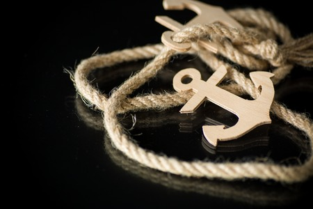 wooden decorative anchor with rope on black