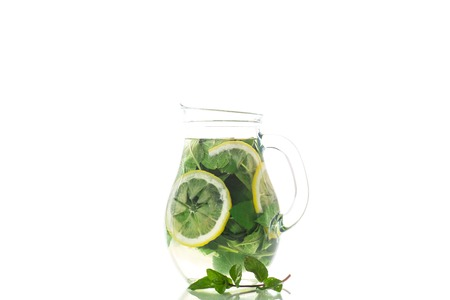 Fresh cold lemonade with lemons and mint in a carafe isolated on white Zdjęcie Seryjne