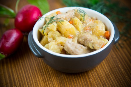 stewed potatoes with vegetables, cabbage and meat in a bowl on a wooden table