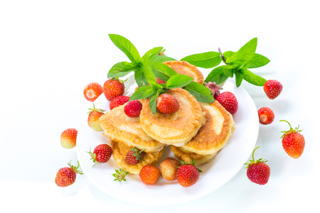 fried sweet pancakes with ripe strawberries in a plate isolated on white background