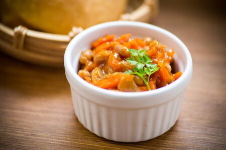stewed diet beans with vegetables in a bowl on a wooden table