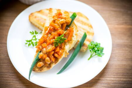 fried bread toasts with stewed beans and vegetables in a plate