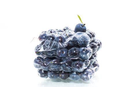 ripe juicy plum in a vacuum bag isolated on white background