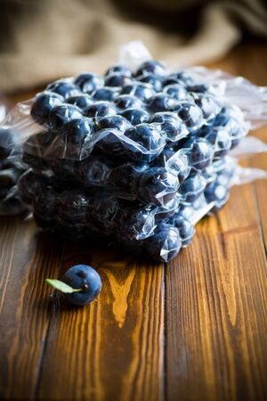 ripe juicy plum in a vacuum bag on a wooden table