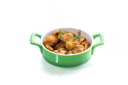 chicken fried in batter with dill on a plate,isolated on white background