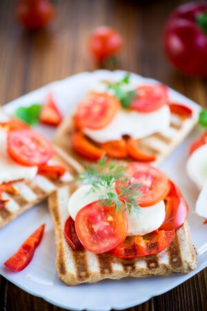 Closeup of a fresh sandwich with mozzarella, tomatoes , on a wooden table. Stockfoto - 129230516