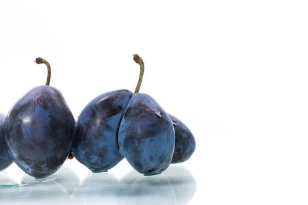 A lot of ripe organic plums isolated on a white background.