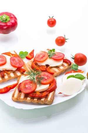 Closeup of a fresh sandwich with mozzarella, tomatoes , on a white background. Stockfoto - 129231681