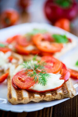 Closeup of a fresh sandwich with mozzarella, tomatoes , on a wooden table. Stockfoto - 129231685