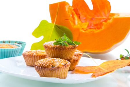 baked sweet pumpkin muffins with dried apricots inside, isolated on white background