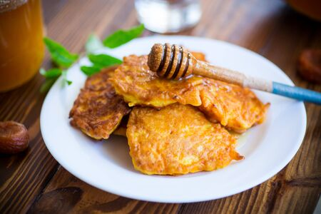 tasty fried sweet pumpkin pancakes with honey on a wooden table