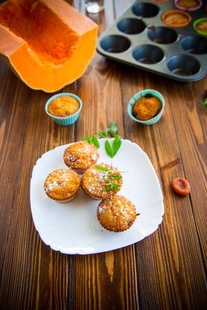 baked sweet pumpkin muffins with dried apricots inside, on a wooden table.