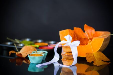 baked sweet pumpkin muffins with dried apricots inside, isolated on black background
