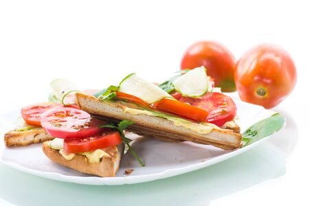 tasty sandwich with curd paste, fresh cucumbers and tomatoes on a white background