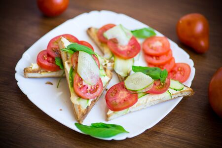tasty sandwich with curd paste, fresh cucumbers and tomatoes on rustic wooden table
