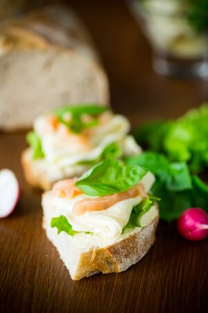 sandwich with cheese, salad leaves and red fish on a wooden table Stockfoto