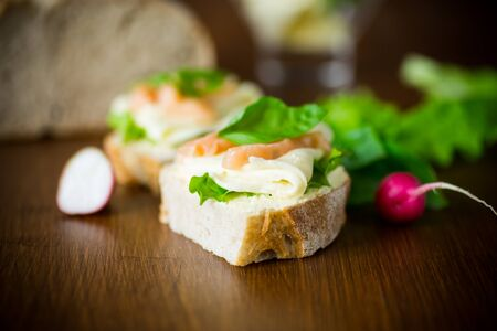 sandwich with cheese, salad leaves and red fish on a wooden table Zdjęcie Seryjne