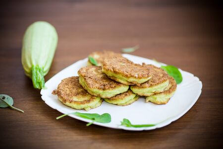 vegetable fritters made from green zucchini in a plate on a wooden background