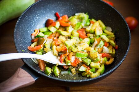 fried zucchini with red pepper, onions, tomatoes and other vegetables in a pan