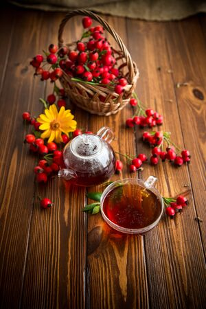 hot tea from medicinal fruits of red ripe rosehip, on a wooden table