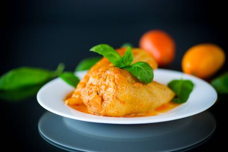 stuffed pepper with meat and vegetable sauce in a plate on black background.