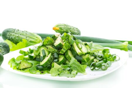 fresh salad of cucumbers and greens in a plate isolated on white background