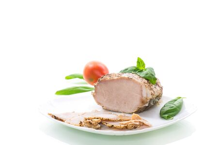homemade baked meat with spices iin a plate on white background.