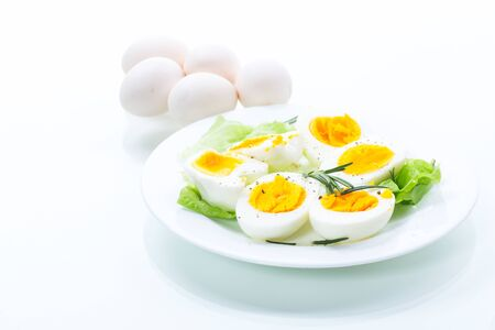 boiled eggs with lettuce in a plate on a white background Banque d'images