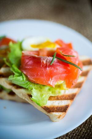 fried bread toast with salad leaves and salted red fish on a wooden table Stock Photo